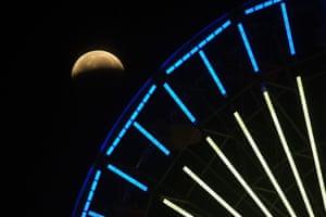 The lunar eclipse shines behind a ferris wheel in Santa Monica, California.