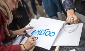 A woman writes the '#Metoo' slogan on a placard during a rally in Paris