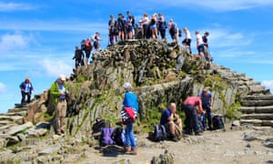 Walkers crowd on to the summit point,  Snowdon