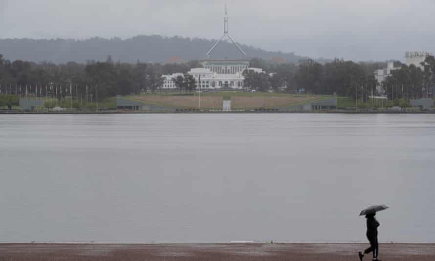 People walk around Lake Burley Griffin in Canberra as rain falls