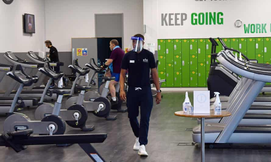 A member of staff wearing a protective face visor in the gym at Kensington Leisure Centre in west London