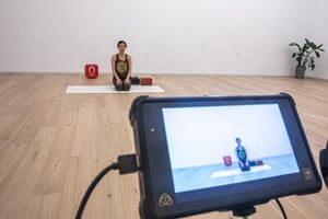 A yoga teacher during the online yoga class at a studio, in Beijing, China. Online classes are becoming more popular in China in the aftermath of the coronavirus outbreak.