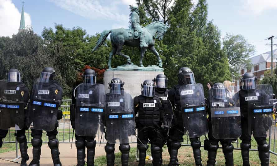 Police stand in front of the Charlottesville statue of Robert E Lee in August 2017.