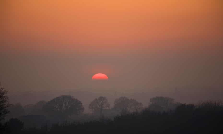 Sun setting over a dark wooded valley near Hawkhurst, Kent.