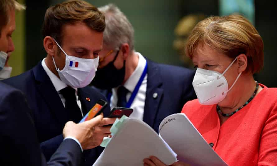 Germany's Angela Merkel and Emmanuel Macron in masks, talking