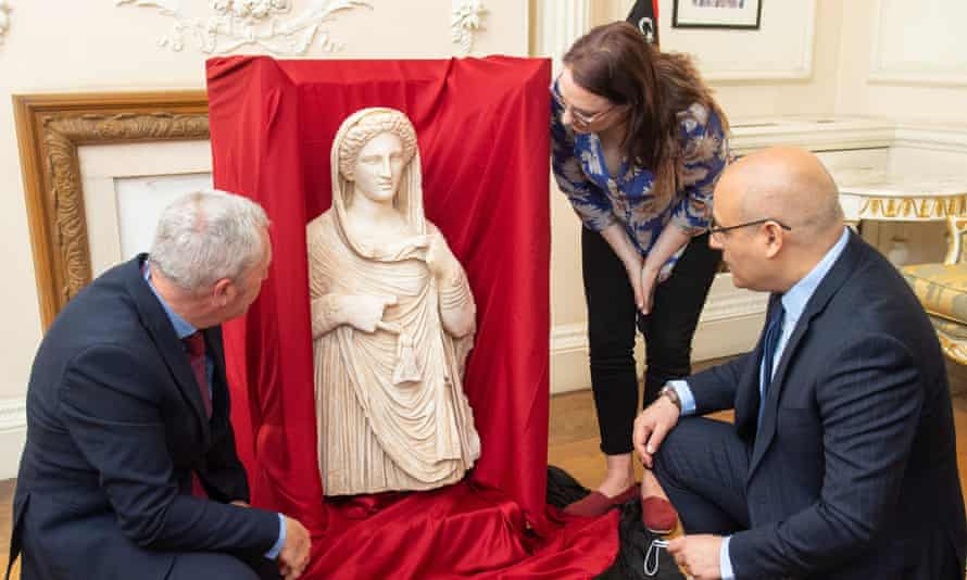 British Museum staff Peter Higgs (left) and Hannah Boulton with Libyan embassy charge d'affaires Mohamed Elkoni view the statue at the Libyan embassy in London.