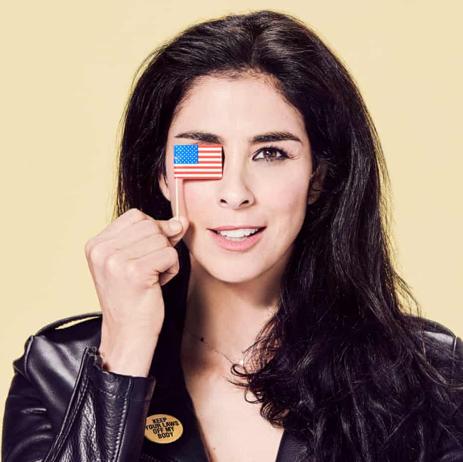 Sarah Silverman wearing a leather jacket and holding a tiny American flag