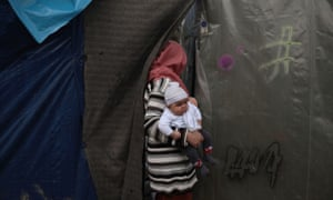 A woman holds a baby as she enters her tent at a makeshift camp for refugees and migrants, next to the Moria camp in Lesobs.