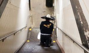 A man descends a subway entrance in Queens