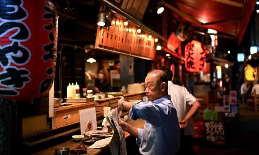 A man reading a newspaper in a Shimbashi izakaya in June last year.