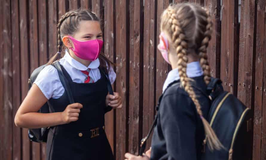 Two 10 year old school friends chatting to each other and wearing face masks