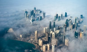 An aerial view of high-rise buildings emerging through fog covering the skyline of Doha.
