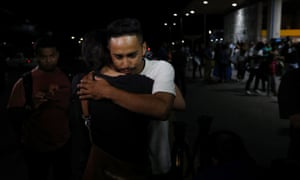 Arnovis Guido is comforted by a friend after being reunited with his daughter in San Luis Talpa, El Salvador, on 28 June.