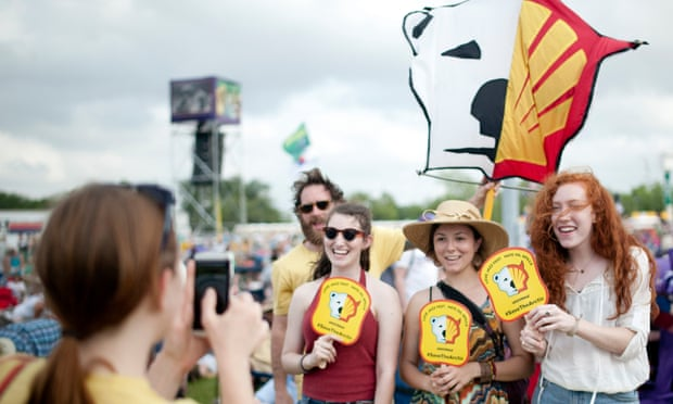 Teenagers pose for a picture under the Shell logo sign at the 45th Louisiana Jazzfest. Greenpeace appeared to protest against the company's oil drilling project in the north of Alaska. Shell later abandoned the project.