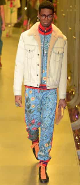 A model on the Gucci catwalk in heavy glasses, a white bomber jacket and floral tracksuit