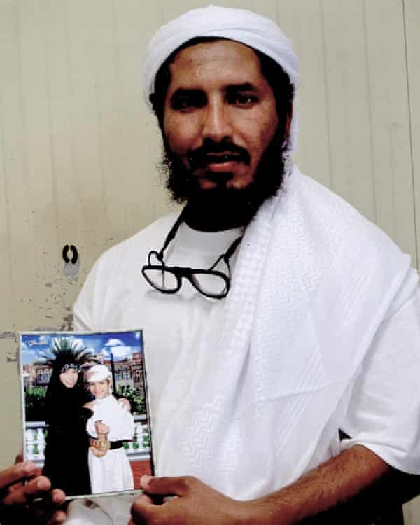 Ahmed al-Darbi, holding a photograph of his children, photographed inside Guantánamo.