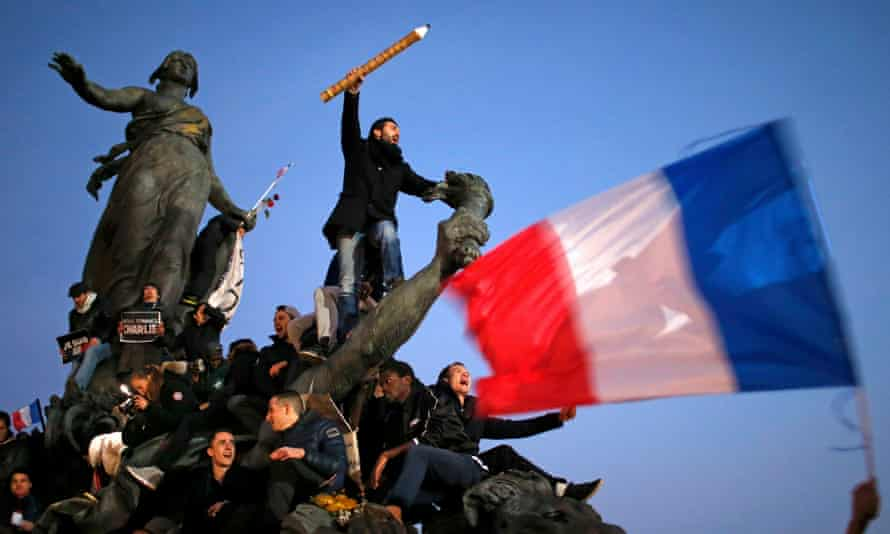 A demonstrator holds aloft a giant pencil during a Paris march on 11 January 2015 in solidarity with the victims of the Charlie Hebdo attack.