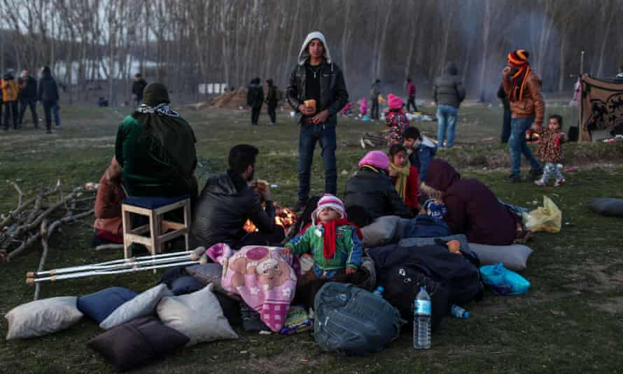 People who have fled Syria rest as they wait to cross the border from Turkey into Greece