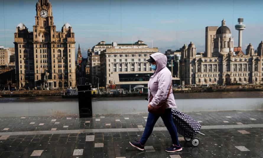 A woman wearing a face mask walks down a street in Liverpool.