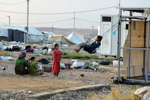 A girl plays on a makeshift swing at a camp in Hamam al-Alil, Iraq