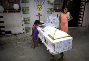 Shara Altuve, 12, right, stands by the coffin of her 11-year-old brother Erick during his wake in a small plaza near their home in the Petare shantytown in Caracas, Venezuela