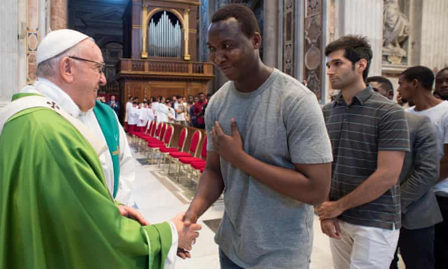Pope Francis is greeted by a migrant at a mass to commemorate the fifth anniversary of his visit in Lampedusa.
