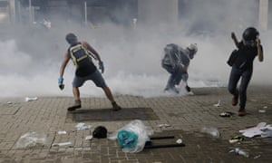 Protesters throw tear gas back at riot police outside the Legislative Council in Hong Kong