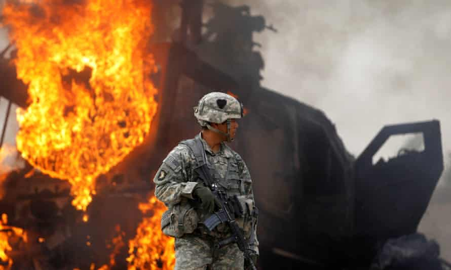 A US army captain stands near a burning armored vehicle destroyed by an improvised explosive device (IED) in the Arghandab Valley north of Kandahar, Afghanistan, in 2010.