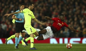 Manchester United's Paul Pogba is upended by Barcelona's Sergio Busquets.