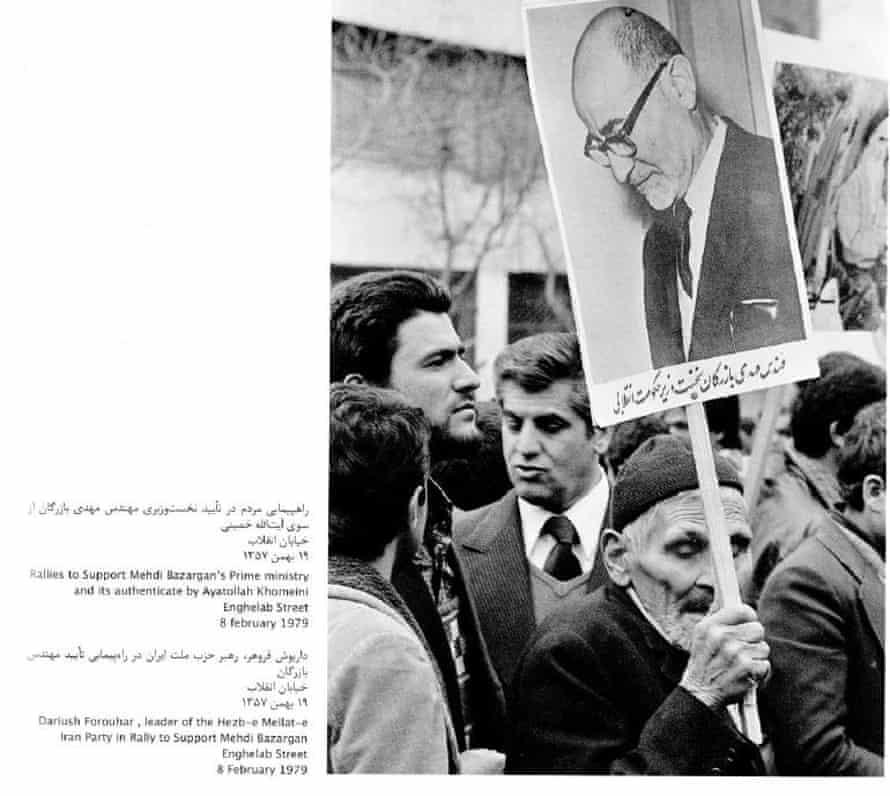 An older man holds up a photo of Mehdi Bazargan