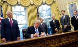 President Donald Trump signs an executive order in the White House on Monday