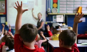 Children raise their hands to answer questions in a primary school
