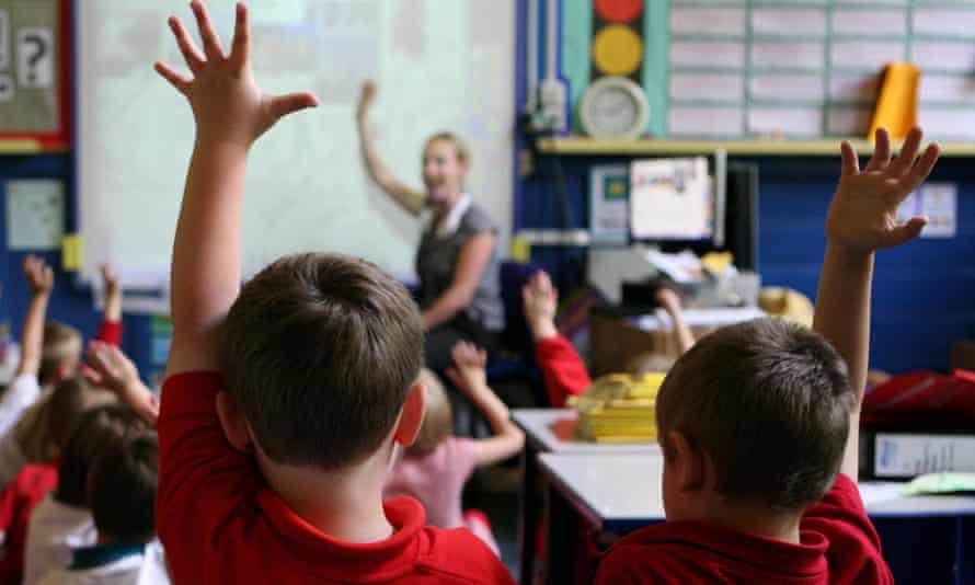 Pupils raising hands in classroom