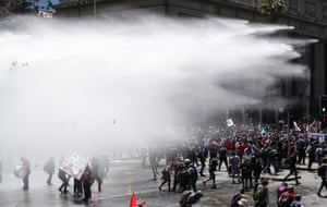 Demonstrators run away after being sprayed by security forces using water cannon