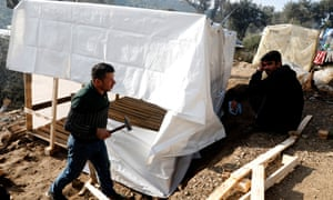 Migrants build a shelter at the makeshift camp. Only those with money can access building materials.