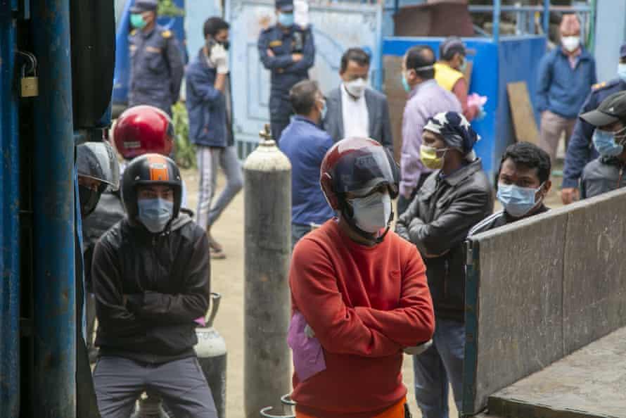 People wait to refill oxygen cylinders in Kathmandu, 13 May