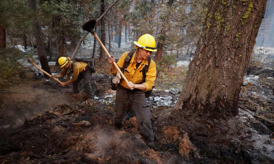 Firefighters Stephanie Lockhart and Dustin Peters of North Tahoe Fire break up smoldering areas after the Caldor fire moved through the area, in South Lake Tahoe, California, on Wednesday.