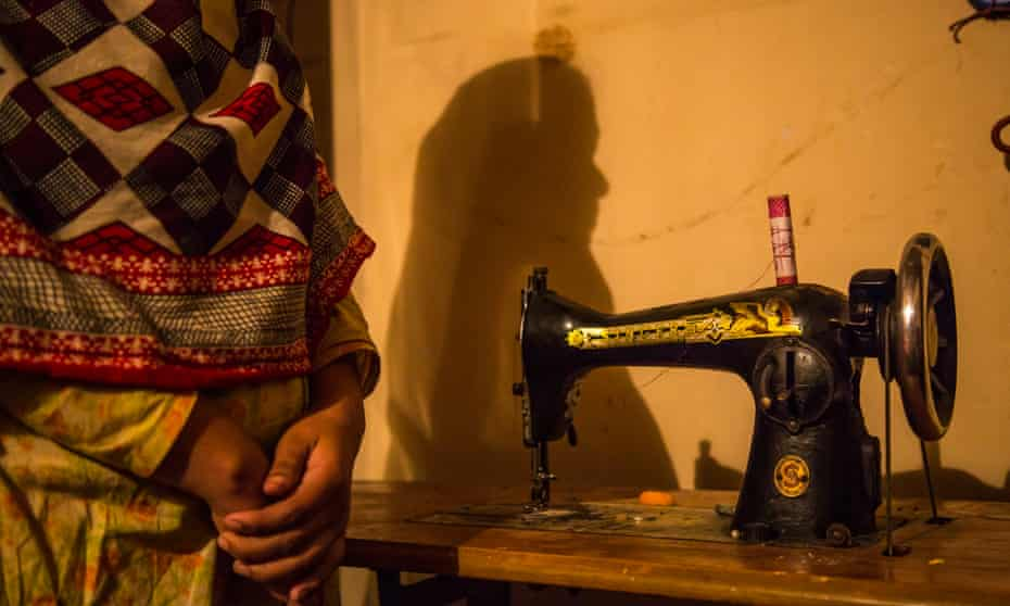 A garment worker, not fully pictured, next to a sewing machine