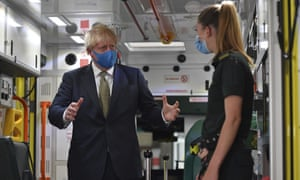 Boris Johnson, wearing a face mask, talks with a paramedic as they stand inside the back of an ambulance during a visit to the headquarters of the London Ambulance Service NHS Trust in London on Monday.
