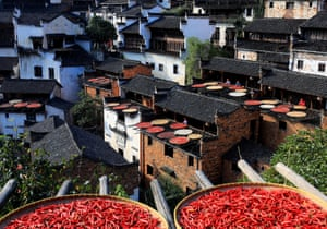 Shangrao, China: Villagers air red chillies, corn, pumpkins and other crops on wooden shelves