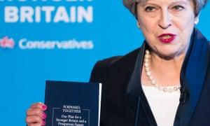 Theresa May holds up the dark blue-bound Tory manifesto