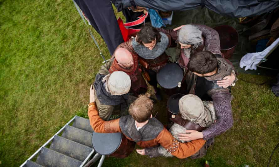 Actors huddle before beginning a costumed run-through during rehearsals at the Stanley Hall base camp in Essex