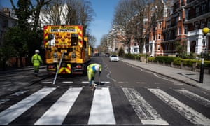 A maintenance team takes advantage of the lockdown and quiet streets to re-paint the iconic Abbey Road crossing.