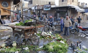 People inspect a site after it was hit by what activists said were forces loyal to Bashar al-Assad.