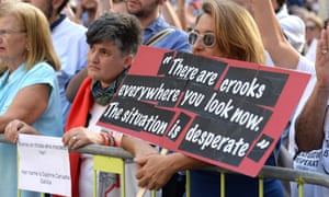 A woman holds a banner with a quote from murdered Maltese journalist Daphne Caruana Galizia at a rally.