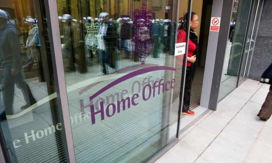 Police officers walk past the the Home office in London