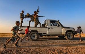 Children run past a gun-mounted truck