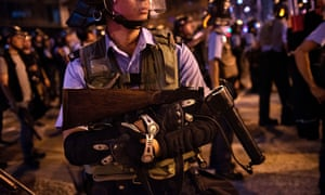 A Hong Kong riot police officer carries supplies to the front line during the clash with protesters.