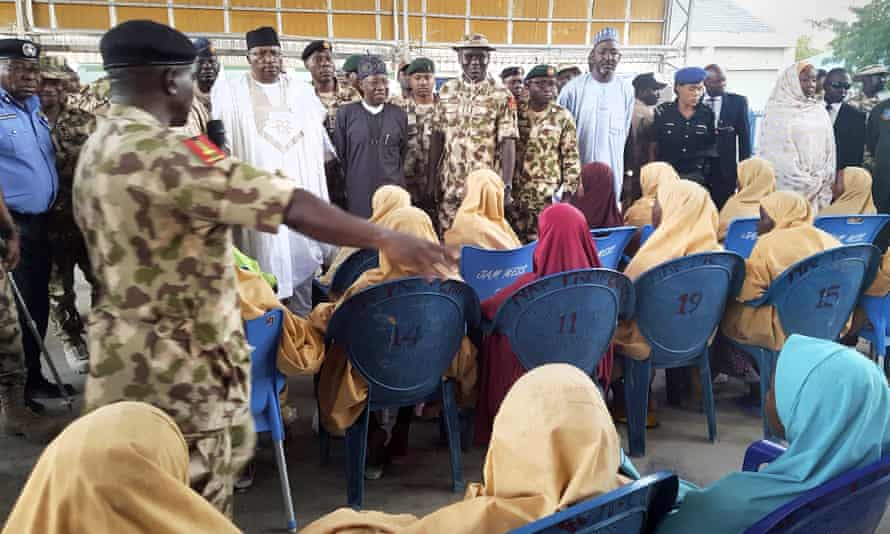 Kidnapped schoolgirls sit down during a handover to government officials in Maiduguri on 21 March.