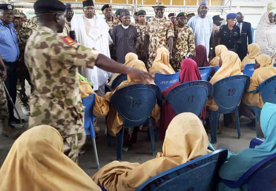 The girls who were kidnapped and released are seated during a hand over to government officials in Maiduguri.